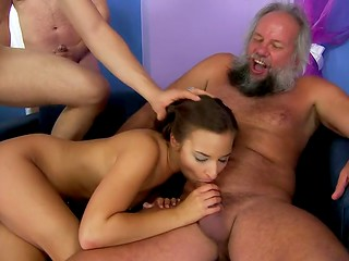 Three dudes are waiting their turn while bewitching cutie is doing mouthjobs