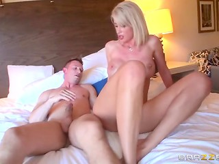 Good-looking blonde MILF with huge tits rides handsome man's erected penis