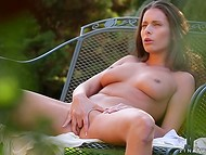 Teenage bombshell is sitting in the fresh air and slowly rubbing her shaved front hole