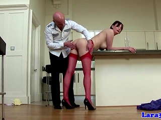 Provoking whore in red lingerie seduces a bald-headed guy in the kitchen