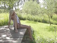 Charming Swedish teen crouched down on the tiny wooden bridge to rub her clitoris