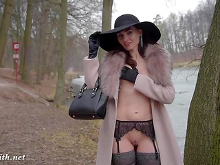 Elegant Jeny Smith in erotic stockings walks around Russian park and flashes pussy and tits