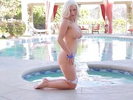 Magnificent blonde Amy Lee with astonishing breasts strips defiantly by the pool