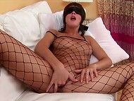 Blindfolded lass in fishnet bodystocking plays with banana and touches trimmed pussy