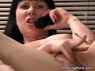 Black-haired MILF talks on the phone, smokes and rubs cunny at the same time