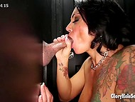 Skilled cocksucker with colored tattoo was sitting in armchair when the first cock appeared from gloryhole 11