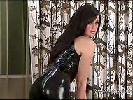 Dark-haired model looks great posing in latex outfit that emphasizes her slender body 10