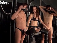 Lustful mistress in black stockings brought two buddies in the secret room to make them obedient