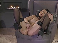 When dark-haired candy gets bored she puts on sexy outfit and fingers pussy by the fireplace 5