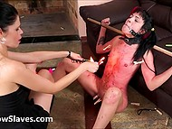 Dark-haired mistress poured hot wax on the body of submissive with bright red hair on the right side of the head 11