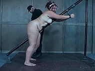 Guy in boilersuit chained helpless fatty woman to handrail and spanked her buttocks with cane