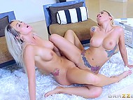 Golden-haired girlfriends actively rub shaved vaginas against each other on the soft carpet 11