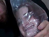 Bearded man with cap tickled red-haired captive, hit the thoracic cage, and put plastic sack on her head 10