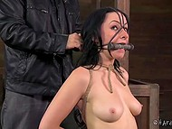 Bearded master with cap skilfully tied up submissive girl and put a piece of wood in mouth 11