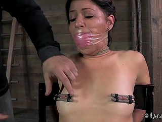 Dominating man put clamps on nipples of captive with gagged mouth and then came back with some toys