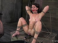 Black-haired prisoner gets tied up in dungeon and vicious man punishes her with adult toys