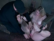 Blonde that is fixed in a slave frame gets an extreme pleasure and screams because of vibrator and dildo in her cunt