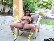 Tootsie exposed natural breasts and spread her legs widely to finger pussy under the canopy 5