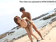 Two men are nailing hairy hole of Japanese in red bikini until they cum inside on the beach