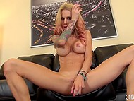 Tattooed blonde relaxes and plays with her tight pussy on the large black sofa 9