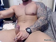 Bearded bruiser with inked hand aims webcam at his penis and jerks it off to entertain viewers