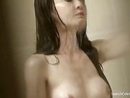 Long-haired Asian cutie washes her body in a shower and shows her sexy body