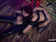 Red-haired slave does everything that dominant want so she blows another slave's cock in leather mask