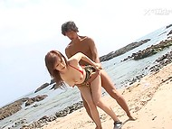 Beautiful busty Japanese is having good time on seashore along with two lovers 5