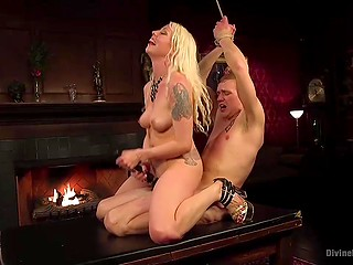 Domineering blonde in high heels takes advantage of young guy's dick by the fireplace