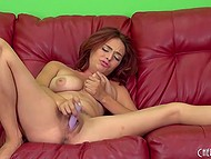 Naughty female slowly masturbates unshaven hole using adult toy on red couch