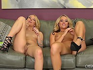 Blonde girlfriends in high heels carefully work with tongues and fingers on couch