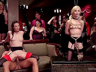 Tied up blonde holds trays while seductive girlfriend gets screwed in front of curious visitors