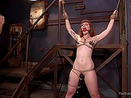 Despite the fact of flogging and clothespins, red-haired girl is trying to smile and get pleasure