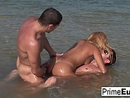Pretty blonde and two muscular guys practice double penetration right in water