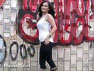 Britain flasher with dark hair tickles her pussy and boobs by the wall painted with graffiti 11