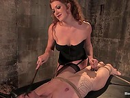 Red-haired girl in fashioned lingerie spanked tied up dude with whip and even helped him to cum