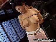 Imperious mistress from Japan exposes servitor's big boobs and pussy hanging her with rope