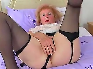 Old woman with red hair stimulates her pierced vagina with metallic dildo in solo porn video