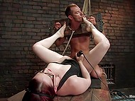Imperious redhead has total control over submissive slave who is tied in dungeon