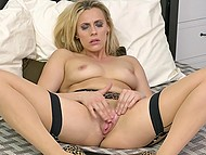 Blonde MILF in stockings and leopard shoes makes herself comfortable in bed to stimulate pussy 7
