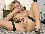 Blonde MILF in stockings and leopard shoes makes herself comfortable in bed to stimulate pussy 8