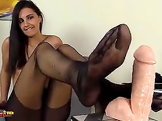 Vicious brunette teases flesh-colored dildo with slim feet in tight black stockings