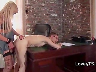 Office worker with glasses lays on table to endure anal punishment from transsexual boss