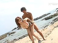 Two unashamed fellows drill Japanese chick with big breasts on sandy beach