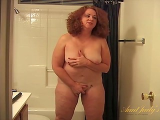 Curly-haired BBW ginger is alone in bathroom where she masturbates with dildo