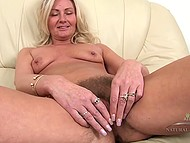 Winning mature lays on couch and gently widens her hairy pussy with fingers 6