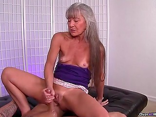 Mature woman with gray hair knows better than young girls how to give handjob
