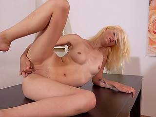 Slim blonde with lovely face laid on table and properly fingered smooth vagina