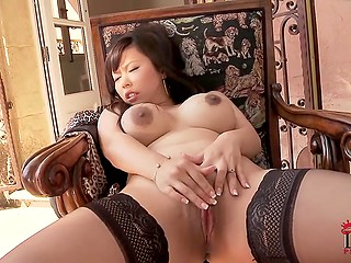 Voluptuous Chinese sexpot turns pierced pussy on with fingers in luxurious armchair