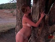 Suntanned girl with pretty face walked down the hill then leisurely undressed by tree 10